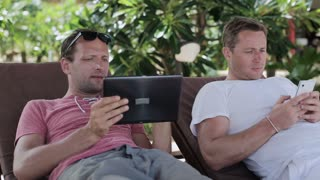 Men working on tablet and smartphone, lying on sunbeds, steadycam shot