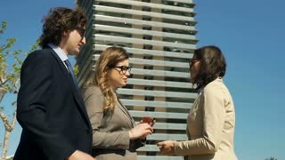 Morose businesspeople talking while having an appointment outdoors, steadycam sh