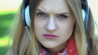 Morose girl listening music on headphones and looking to the camera