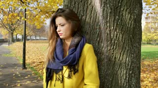 Morose woman leaning on tree in the park and thinking