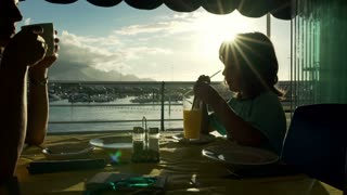 Mother and her son sitting in the restaurant and drinking beverage, steadycam sh