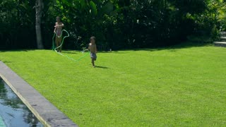 Mother and son having fun in the garden, slow motion