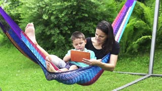 Mother and son using tablet in a hammock, slow motion shot at 60fps