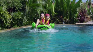 Mother playing with son in the pool, slow motion shot at 240fps