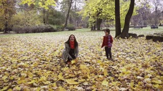 Mother throwing leaves in the air, steadycam shot, slow motion shot at 240fps