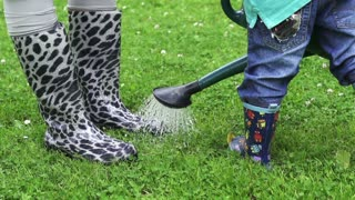 Mother with child playing with a watering can, slow motion shot at 240fps