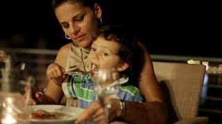 Mother with her son eating dinner on the terrace at night, steadycam shot