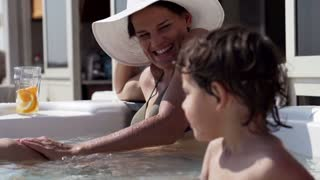 Mother with her son playing in jacuzzi, slow motion shot at 240fps