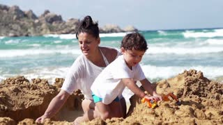 Mother with her son playing on the beach, slow motion shot at 120fps