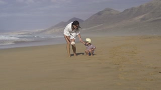 Mother with his son having fun on the beach, slow motion shot at 240fps