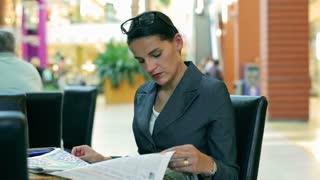 Occupied businesswoman reading newspaper in the restaurant