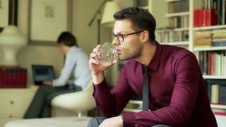 Pensive businessman sitting at home and drinking water