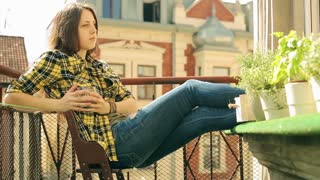Pensive girl sitting on balcony and drinking water