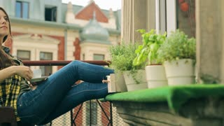 Pensive girl sitting on the balcony and drinking coffee, steadycam shot