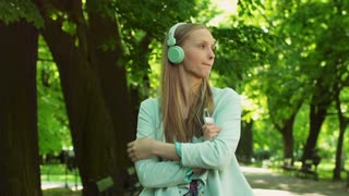 Pensive girl standing in the park and listening music on headphones