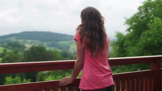 Pensive girl standing on the terrace and thinking