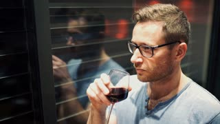 Pensive man leaning on the window and drinking wine alone