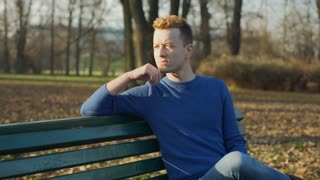 Pensive man sitting in the park and doing morose look to the camera, steadycam s