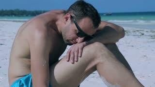 Pensive man sitting on the beach