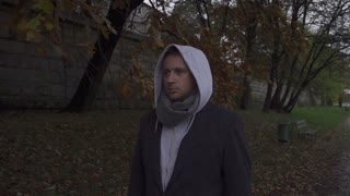 Pensive man with hood walking on pathway, steadycam shot, slow motion  240fps