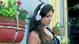 Pensive woman listening music on the balcony, steadycam shot