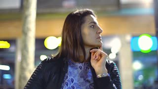 Pensive woman sitting alone in the city at night, steadycam shot