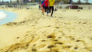 People running on the sandy beach, steadycam shot, slow motion shot