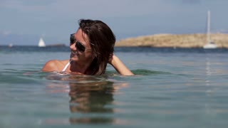 Portrait of beautiful smiling girl in the sea, slow motion shot at 240fps