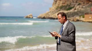Portrait of smiling businessman working on tablet computer on the beach