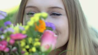 Pretty, blonde girl smiling while holding and smelling bunch of flowers