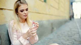 Pretty, blonde girl squats in the alley and drinking cocktail