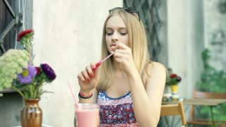 Pretty, blonde girl using lipgloss while painting her lips in the outdoor cafe