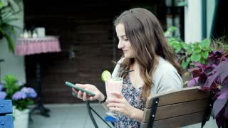 Pretty brunette texting on smartphone and holding cocktail while sitting outside