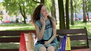 Pretty girl chatting on cellphone while sitting in the park with her shopping