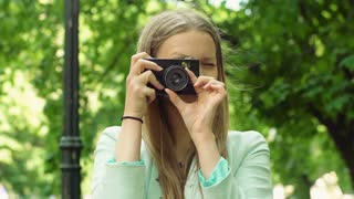 Pretty girl doing photos on old camera and smiling in the park