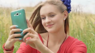 Pretty girl doing selfies on smartphone while sitting in the grain field