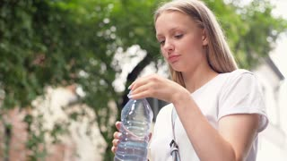 Pretty girl drinking water from a bottle and smiling to the camera