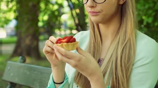 Pretty girl eating cookie with strawberries and smiling to the camera