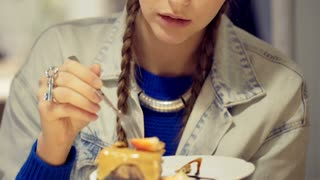 Pretty girl eating delicious cake in the cafe and smiling to the camera, steadyc