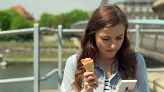Pretty girl eating ice cream and browsing internet on smartphone