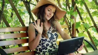 Pretty girl having a videocall on laptop while sitting in the arbor