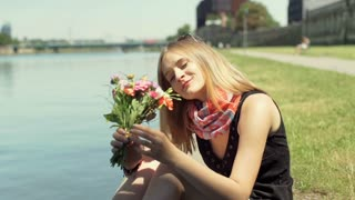 Pretty girl holding bunch of flowers and smiling to the camera by the river