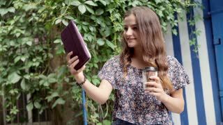 Pretty girl holding coffee and doing selfies on tablet