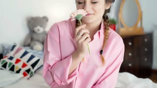 Pretty girl holding flower and smiling to the camera while sitting on bed, stead