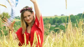 Pretty girl holding scarf and smiling to the camera on the grain field