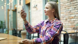 Pretty girl in checked shirt looking happy while doing photos in the cafe