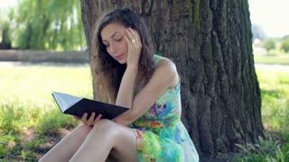 Pretty girl in floral dress having a headache while reading a book