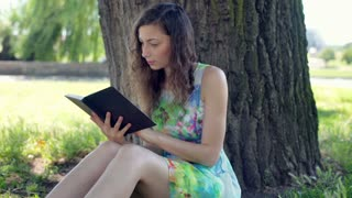 Pretty girl in floral dress reading absrobing book under the tree