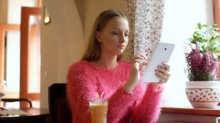 Pretty girl in fluffy sweater browsing internet on tablet and smiling to the cam