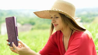 Pretty girl in straw hat doing selfies on tablet while sitting on the meadow